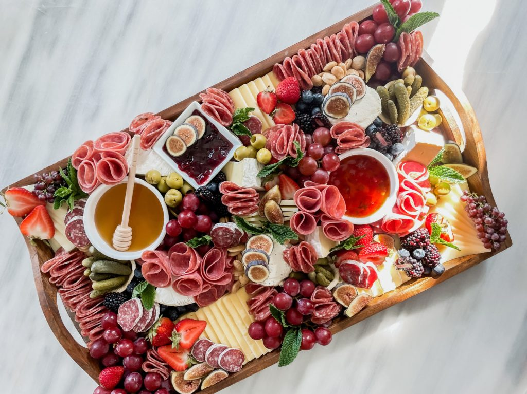 Large shareable charcuterie board with meats cheeses and fruits