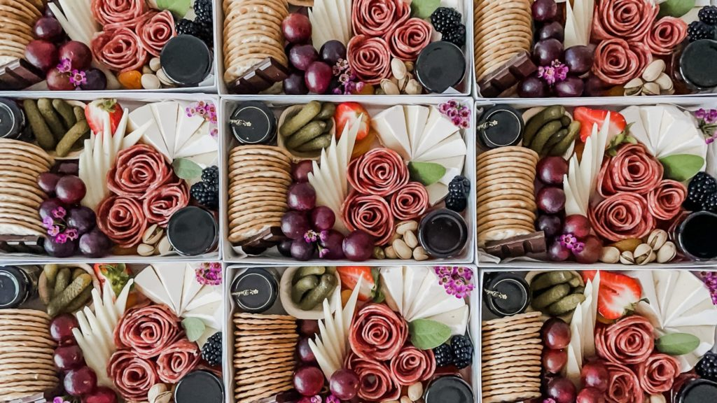 Shareable charcuterie boxes with meats cheeses and fruits